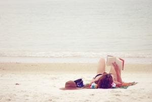sunbather on beach with book